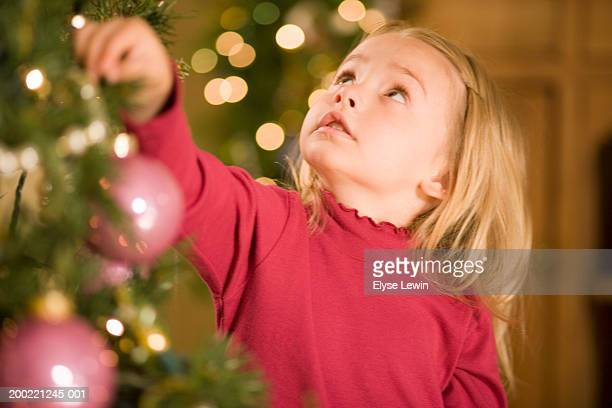 Girl (3-5) hanging Christmas tree ornament, looking up