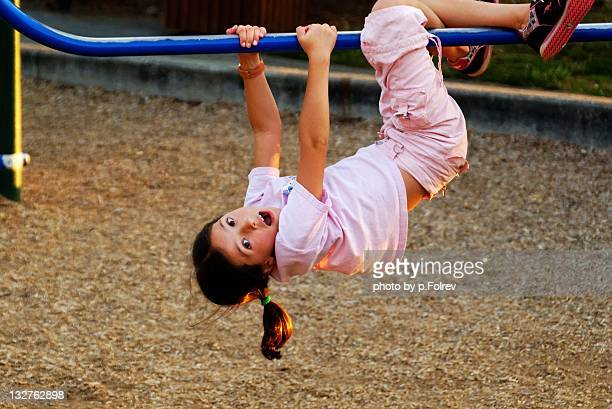 Girl hanging from bar in playground