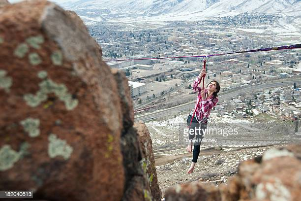 girl hanging off of a high line, over a small town - focus on background ストックフォトと画像