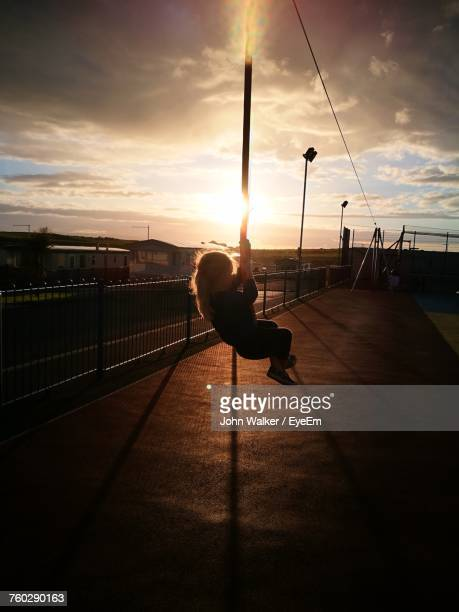 Girl Hanging On Rope During Sunset