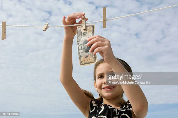 girl hanging one million dollar bill on clothes-line - one million dollar bill stock pictures, royalty-free photos & images