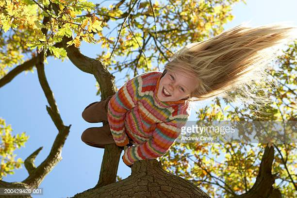 Girl (10-12) hanging upside down from tree, smiling, portrait