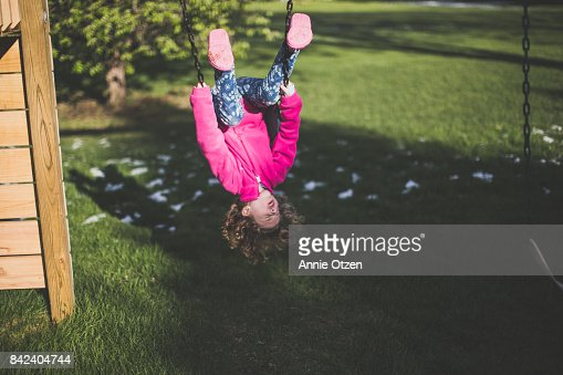 Girl Hanging Upside Down on a Swing