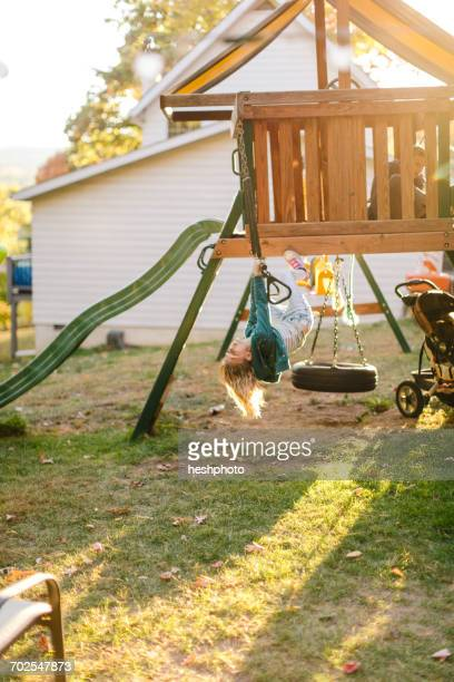 girl hanging upside down on playground equipment in garden - heshphoto stock pictures, royalty-free photos & images