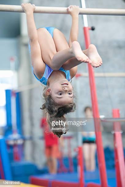 A girl hangs upside down from gymnastics high bar
