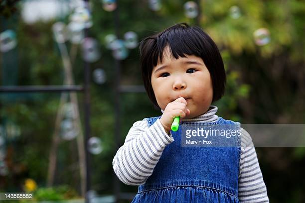 girl happily blowing bubbles - yonago stock photos and pictures