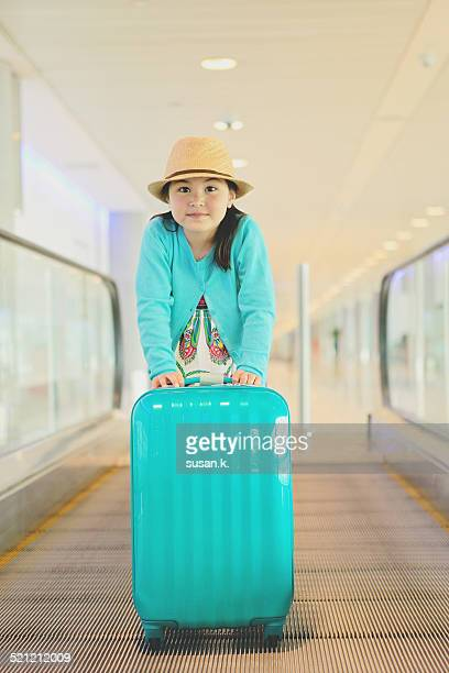 Girl happily pushing her suitcase at the airport