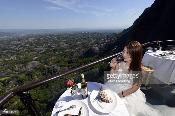 A girl has food and wine on the glass skywalk hanging on a cliff during the debut of a cafe in Shiniuzhai scenic zone on August 29 2016 in Hunan...