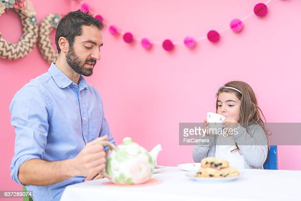Girl having a tea party with her father in a pink