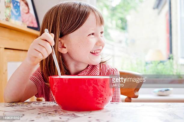 Girl (6-7) having cereals for breakfast