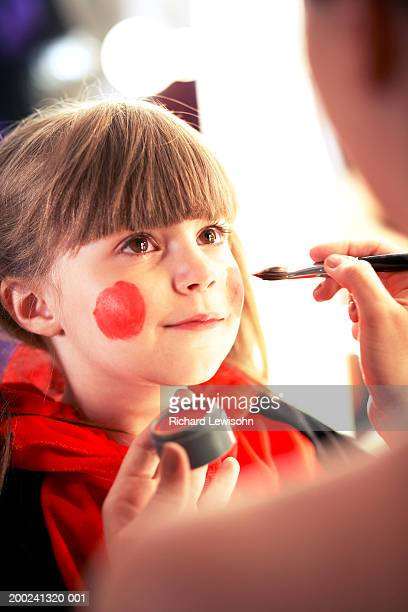 Girl (5-7) having face painted, close-up