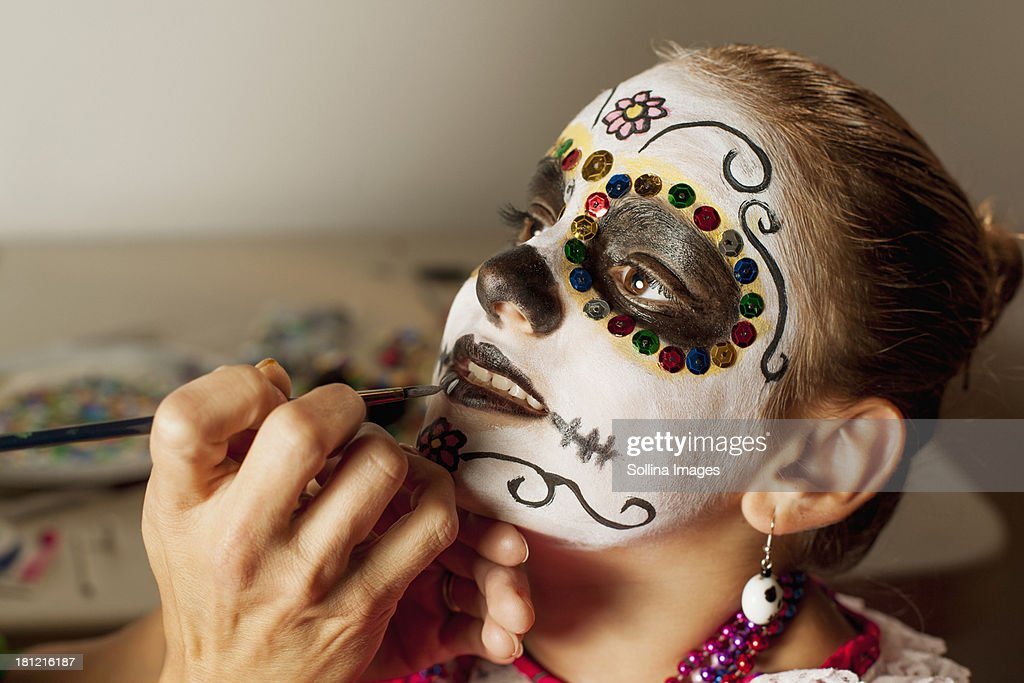 Girl having face painted for Dia de los Muertos : Stock Photo