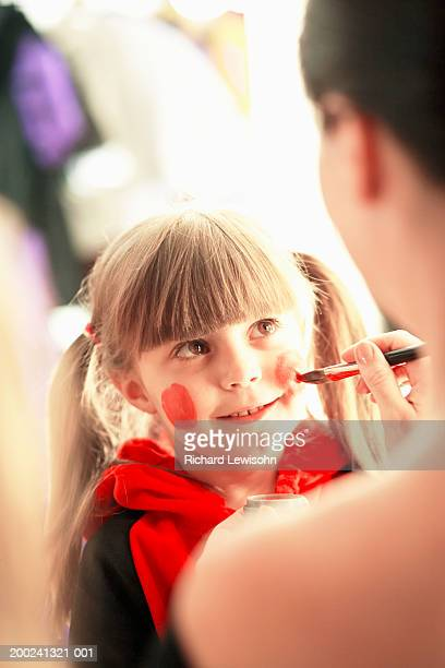 Girl (5-7) having face painted, view over woman's shoulder