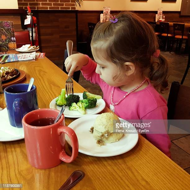 girl having food at restaurant - elena knouzi stock pictures, royalty-free photos & images