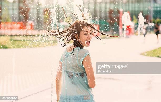 Girl having fun in a water fountain