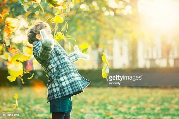Girl having fun in park throwing leaves up in air