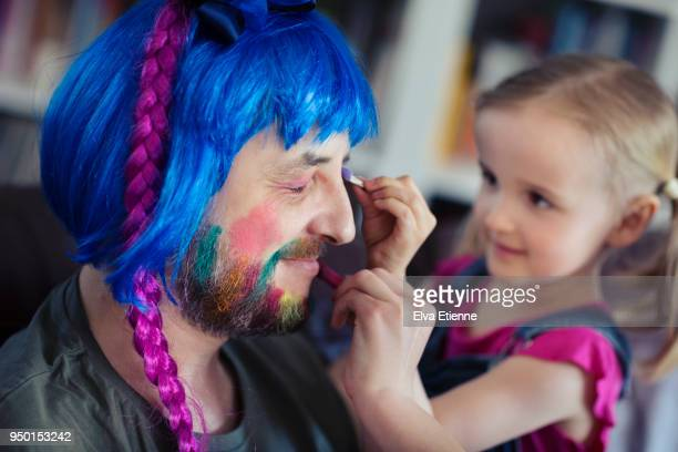 Girl (4-5) having fun putting makeup and wig on her father