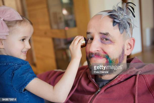 girl (4-5) having fun putting makeup on her bemused father - genderblend stock pictures, royalty-free photos & images