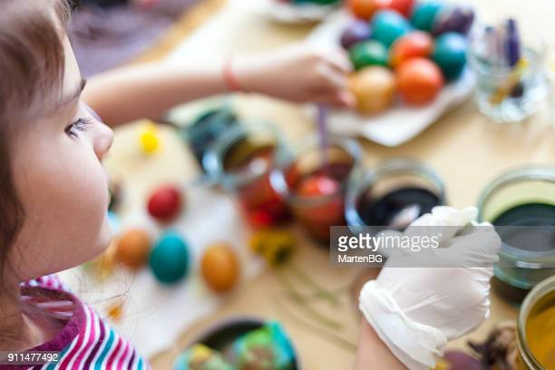 Girl having fun to paint Easter eggs