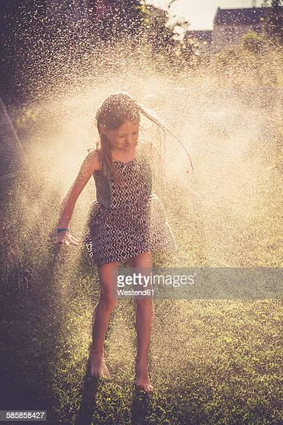 Girl having fun with splashing water in the garden