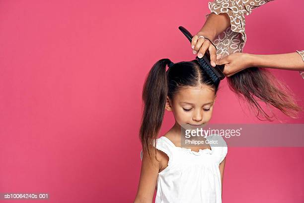 Girl (4-5) having hair brushed by woman