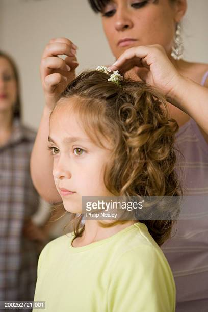Girl (7-9) having hair done, woman helping (focus on girl)