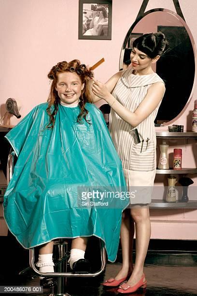 Girl (10-12) having hair styled in beauty salon