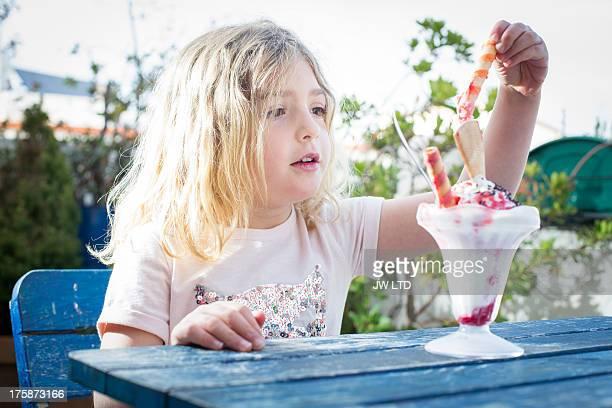 girl having ice cream sundae, summer day - eisbecher stock-fotos und bilder