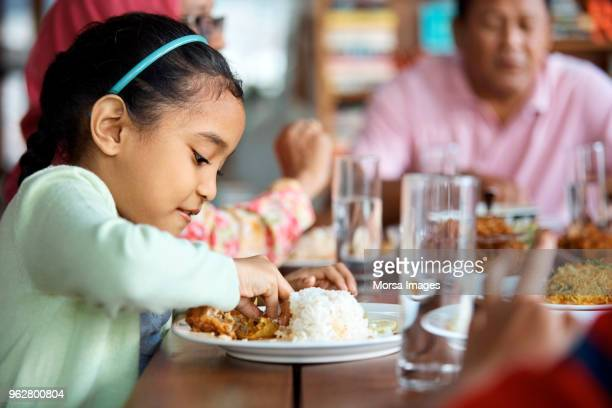 girl having rice and chicken with family at home - malaysian ethnicity stock pictures, royalty-free photos & images