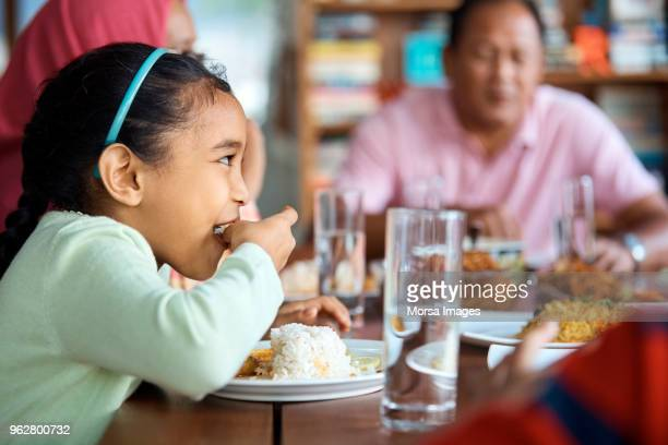 girl having rice with family at home - family at home stock photos and pictures