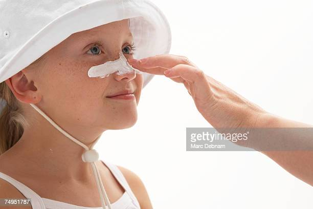 Girl (7-9) having sun cream applied to nose