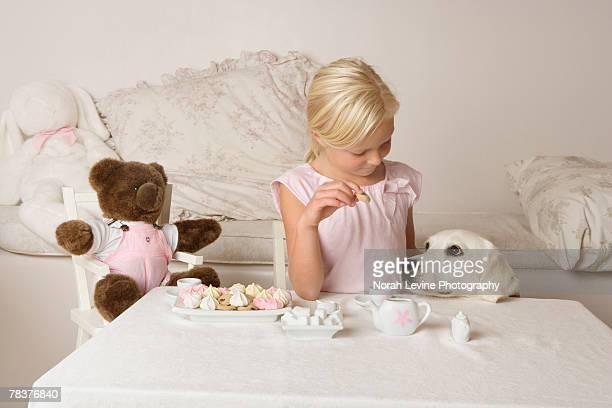 Girl having tea party with teddy bear and dog