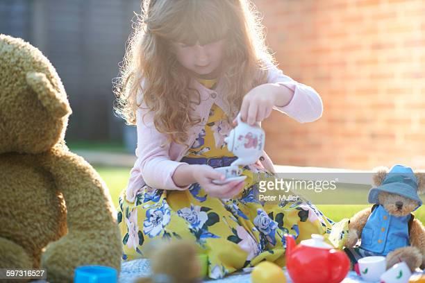 Girl having teddy bear picnic in garden pouring tea