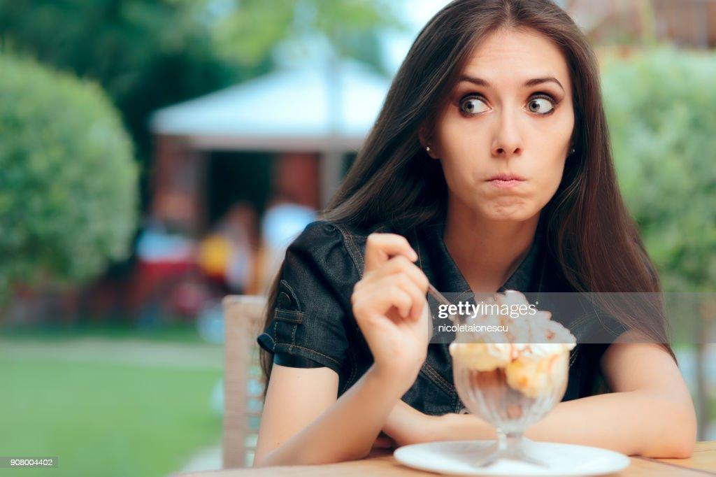 Girl Heisting to a Eat High Calorie Ice Cream Dessert : Stock Photo