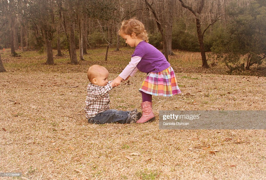 Girl helping boy in standing up : Stock Photo