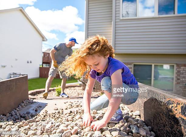 Girl Helping Dad Put Landscaping Rock in Front of House