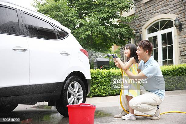 Girl helping father cleaning car