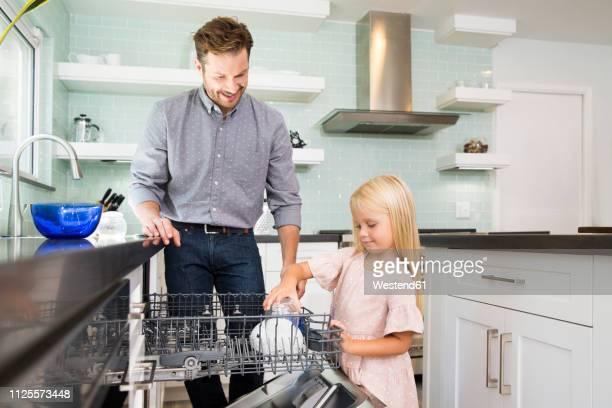 girl helping father clearing the dishwasher in kitchen - familie mit einem kind stock-fotos und bilder