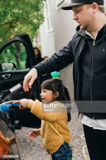 girl helping father in charging car while going for picnic - mensch im hintergrund stock-fotos und bilder