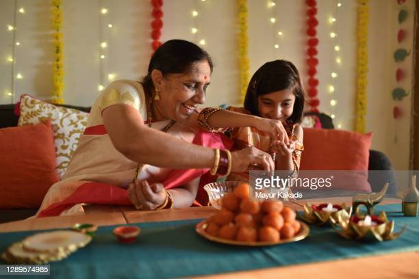 girl helping grandmother in kitchen - celebration stock pictures, royalty-free photos & images