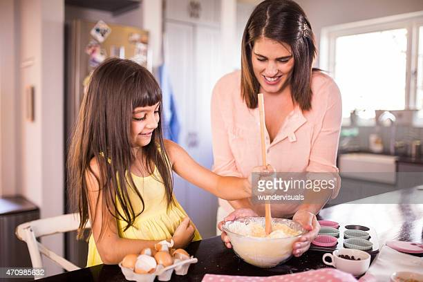 Girl helping her mom by stirring the ingredients for cake