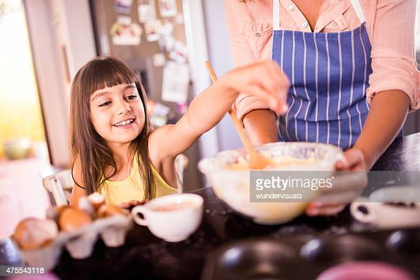 Girl helping mom in the kitchen to bake a cake