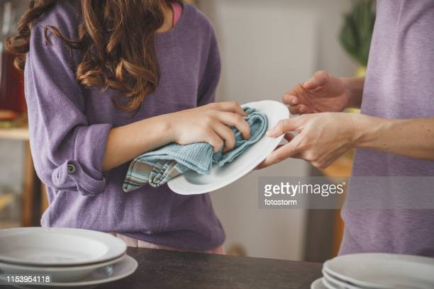 girl helping mother cleaning dishes in the kitchen - dish towel stock pictures, royalty-free photos & images