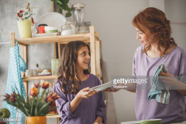 girl helping mother cleaning dishes - dish towel stock pictures, royalty-free photos & images