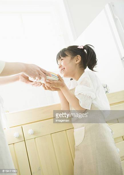 Girl Helping Mother Wash Dishes