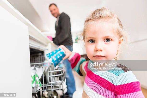 Girl helping to stack dishwasher