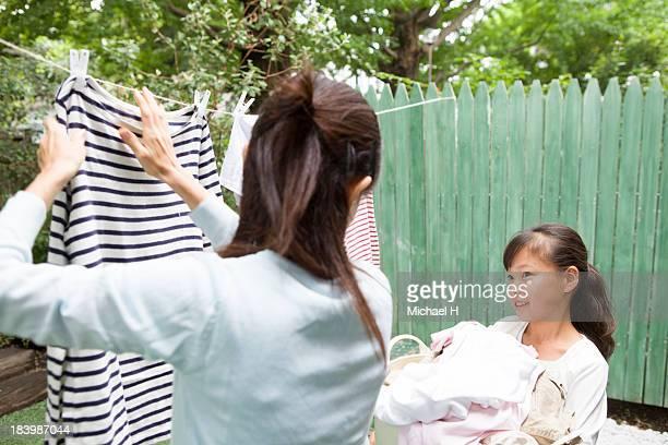 a girl helps grandma's laundry in the garden - 物干し ストックフォトと画像