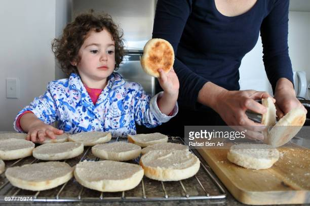 girl helps her mother to prepare breakfast - rafael ben ari stock-fotos und bilder