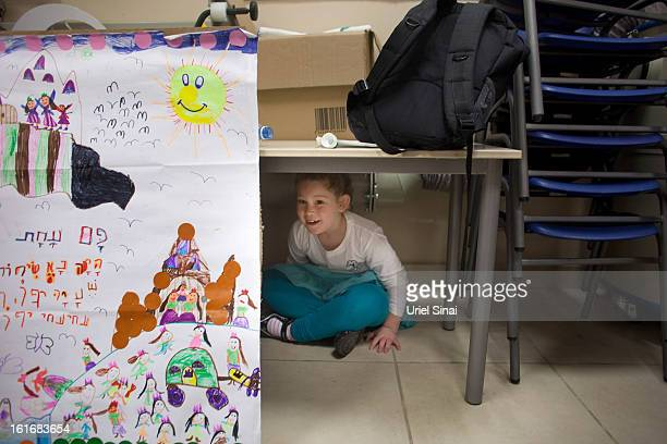 RA'ANANA ISRAEL FEBRUARY 14 A girl hides under a table as Israeli schoolchildren take cover in a bomb shelter during a Home Front command drill...