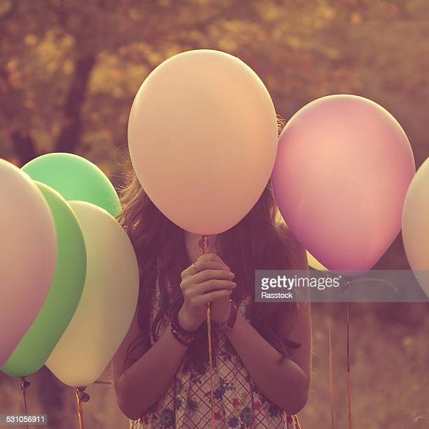 Girl hiding behind balloons
